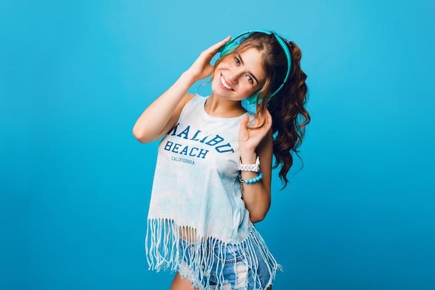 Mooi meisje met lang krullend haar in de staart op een blauwe achtergrond in de studio. ze draagt een wit t-shirt, korte broek en luistert naar muziek met een blauwe koptelefoon. Gratis Foto