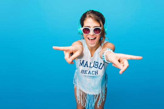 Mooi meisje met lang krullend haar in staart in blauwe zonnebril heeft plezier op blauwe achtergrond in de studio. ze draagt een wit t-shirt, korte broek en luistert naar muziek met een blauwe koptelefoon. Gratis Foto