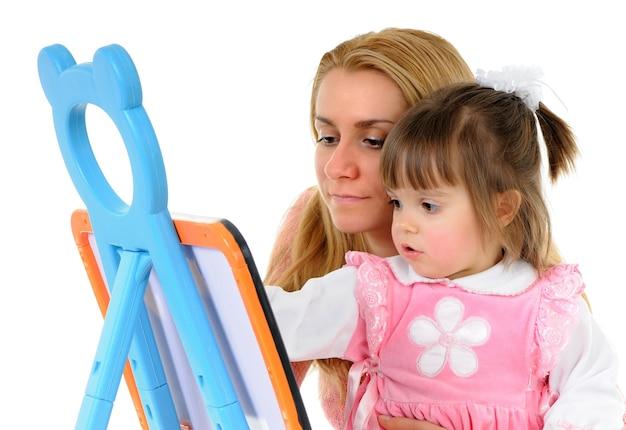 Mooi meisje met moeder tekenen samen op het bord Premium Foto