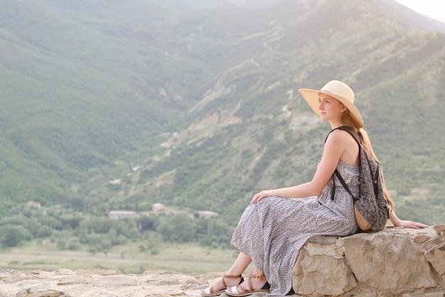 Mooi meisje met rugzak in een brede hoed zittend op bergen Premium Foto
