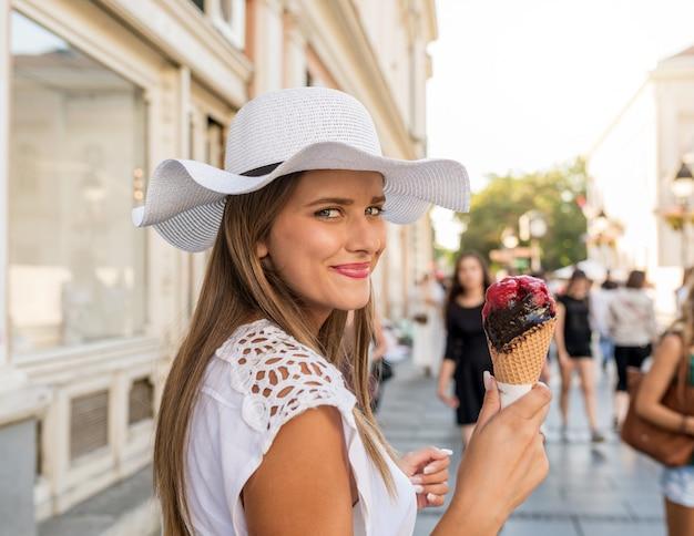 Mooi meisje met witte hoed en boodschappentassen eten van ijs op straat in de stad Premium Foto
