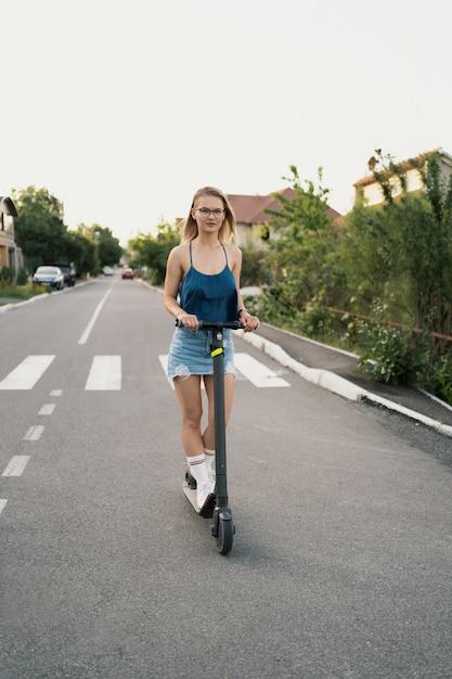 Mooi meisje rijden op een elektrische scooter in de zomer op straat Gratis Foto