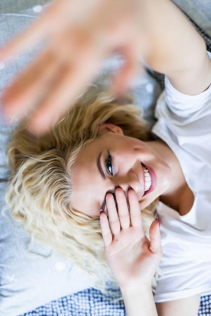 Mooi meisje selfie maken in het bed. mooi meisje die thuis op het bed zelf maken. selfie in de ochtend. mooie jonge vrouw selfie maken terwijl je voor raam Gratis Foto