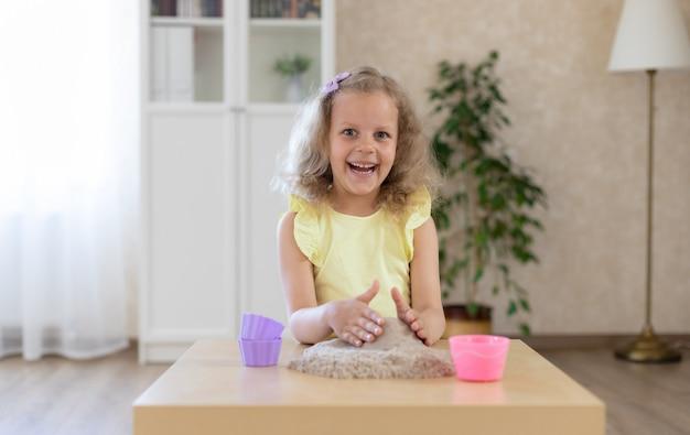 Mooi meisje spelen met kinetisch zand en een schop Premium Foto