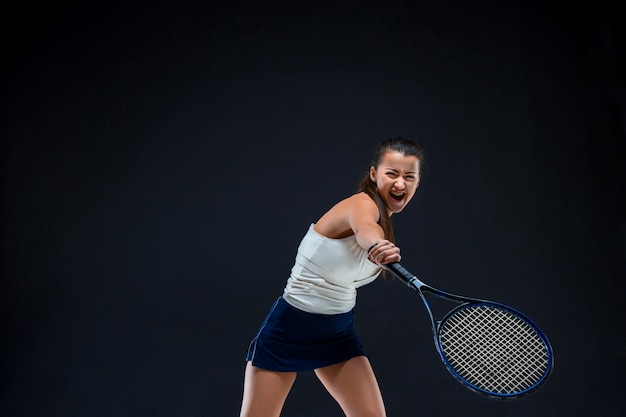 Mooi meisje tennisspeler met een racket op donkere achtergrond Gratis Foto