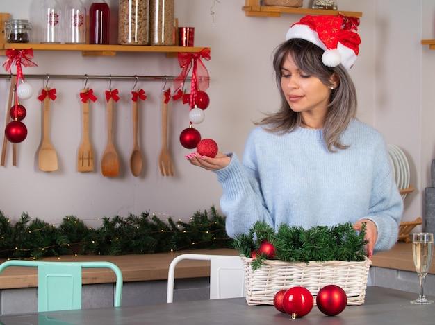 Mooi meisje verkleedt een kerstboom voor kerstmis Premium Foto