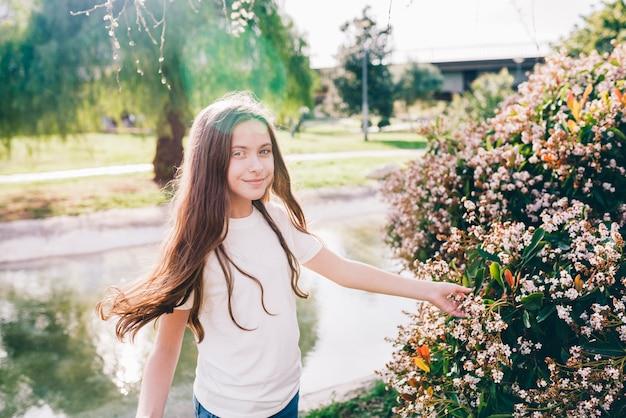 Mooi meisje wat betreft bloemen dichtbij meer in park Gratis Foto