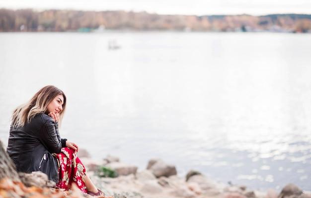 Mooi meisje zit aan de oever van het meer en bewondert het uitzicht op de natuur Premium Foto