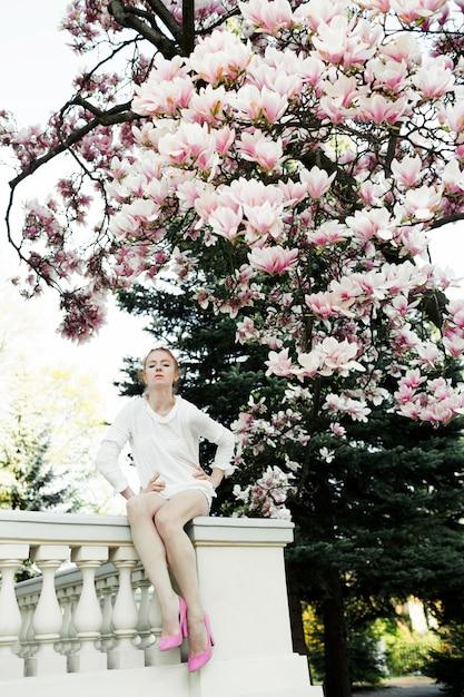 Mooi meisje zit aan de reling onder de geweldige magnoliaboom Gratis Foto