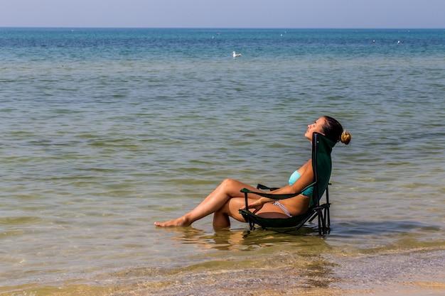 Mooi meisje zit alleen in de zee, mooi bruin Gratis Foto
