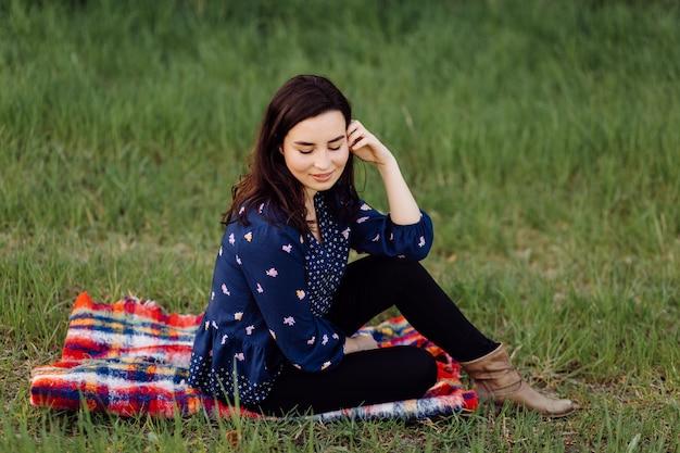 Mooi meisje zit op een plaid in het voorjaar park Gratis Foto