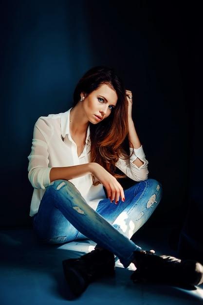 Mooi meisje, zittend op de vloer in het donker Premium Foto