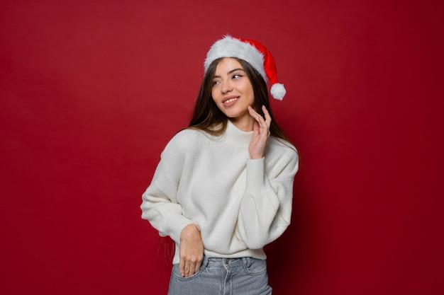 Mooi model in kerstmuts en witte gezellige trui poseren op rood Gratis Foto