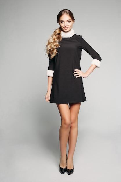 Mooi model met blond golvend haar in staart in mini-zwarte jurk met bonttrim. Premium Foto