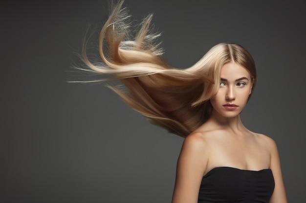 Mooi model met lang glad, vliegend blond haar dat op donkergrijze studioachtergrond wordt geïsoleerd. jong kaukasisch model met goed onderhouden huid en haren die in de lucht blazen. Gratis Foto