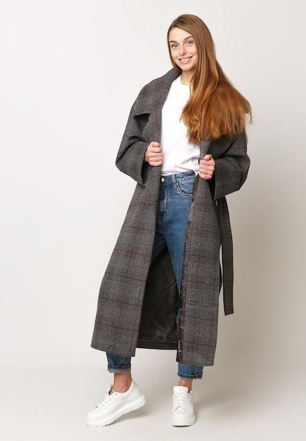 Mooi model poseren in een bruine lange jas op een witte achtergrond. studio opname. kleding reclame concept. Premium Foto