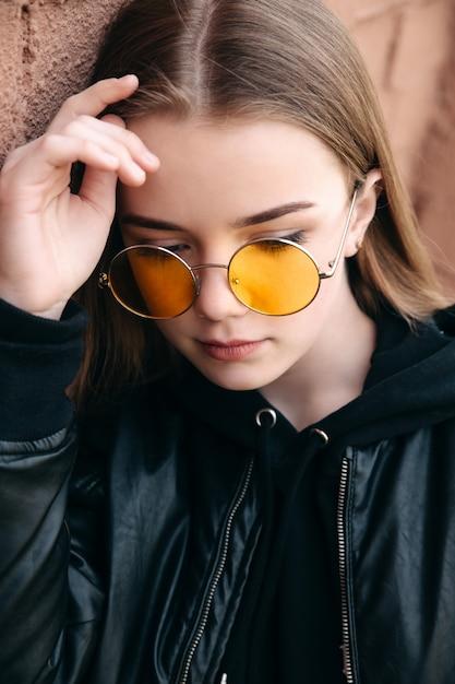 Mooi modieus jong geitjemeisje in gele zonnebril in stadsstraat Premium Foto