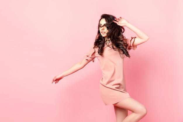Mooi modieus meisje met lang krullend haar in een roze jurk in de studio op een roze achtergrond. Premium Foto