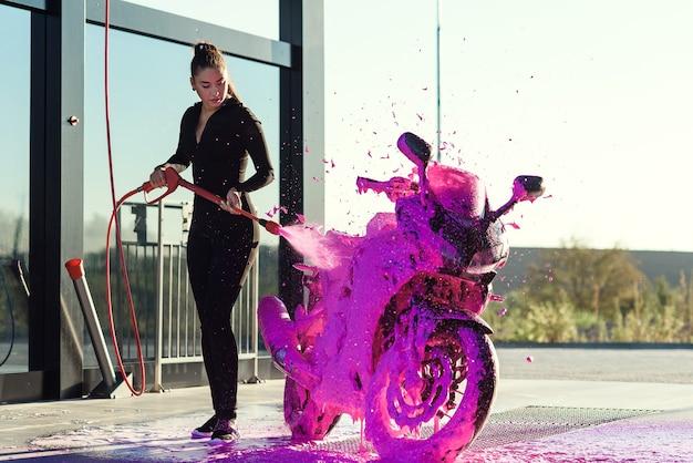 Mooi mooi meisje in strakke verleidelijke pak wast een motorfiets bij self-carwash Premium Foto