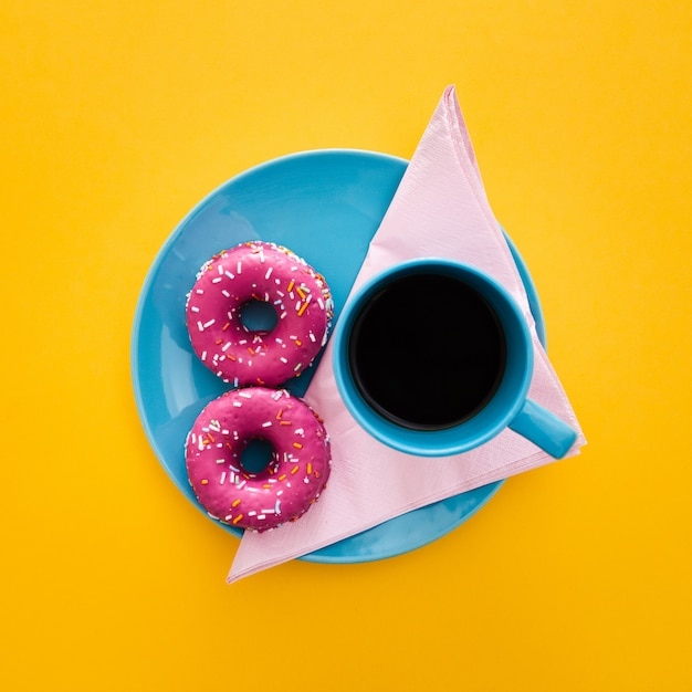 Mooi ontbijt met doughnut en kop van koffie op geel Gratis Foto