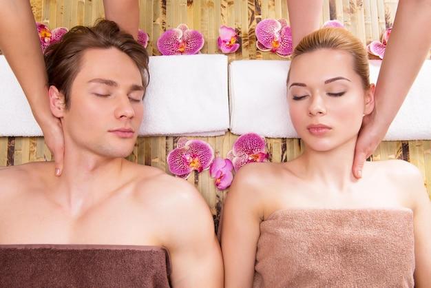 Mooi paar dat in een kuuroordsalon ligt die samen van hoofdmassage geniet. Gratis Foto