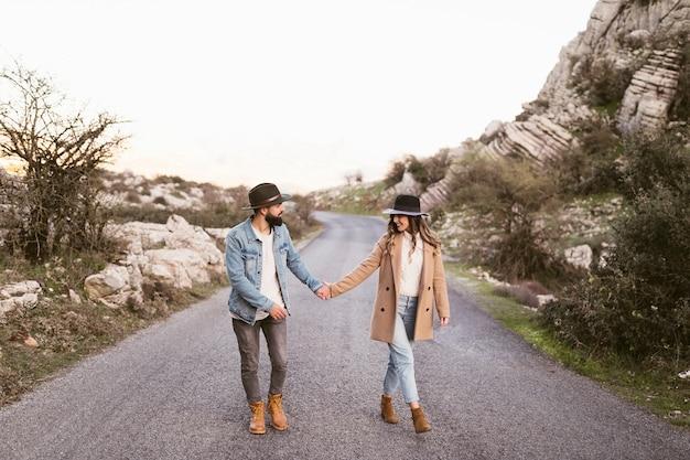 Mooi paar dat op een weg loopt Gratis Foto