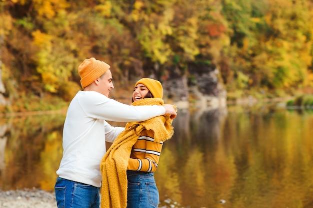 Mooi paar die in liefde in de herfstpark lopen. gelukkig jong koppel plezier samen buitenshuis. liefde, relatie en mode concept Premium Foto