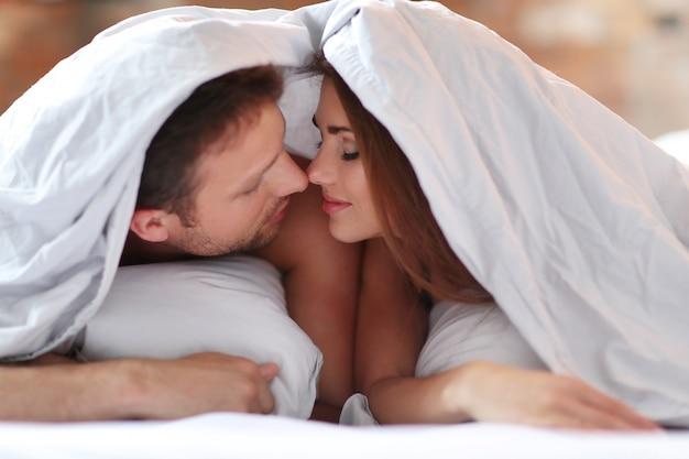 Mooi paar in bed onder de dekens. Gratis Foto