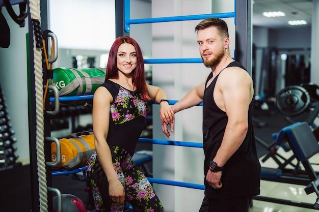 Mooi paar met sterk fysiek lichaam dat zich in de sportclub en het glimlachen bevindt. aantrekkelijke vrouw en gespierde bodybuilder man poseren in de sportschool. Premium Foto