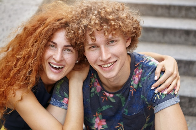 Mooi paar plezier samen zitten op trappen en elkaar omhelzen Gratis Foto