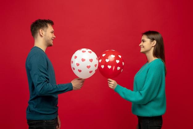 Mooi paar verliefd op ballonnen op rode studiomuur Gratis Foto