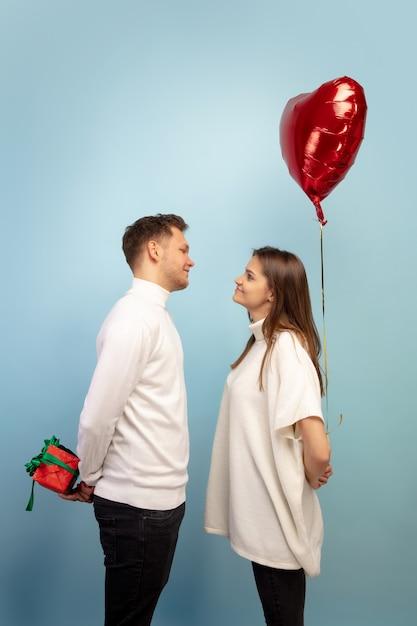Mooi paar verliefd op hartvormige ballon op blauwe studiomuur Gratis Foto