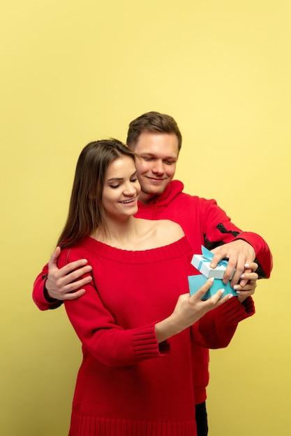 Mooi paar verliefd openen geschenk op gele studio muur Gratis Foto