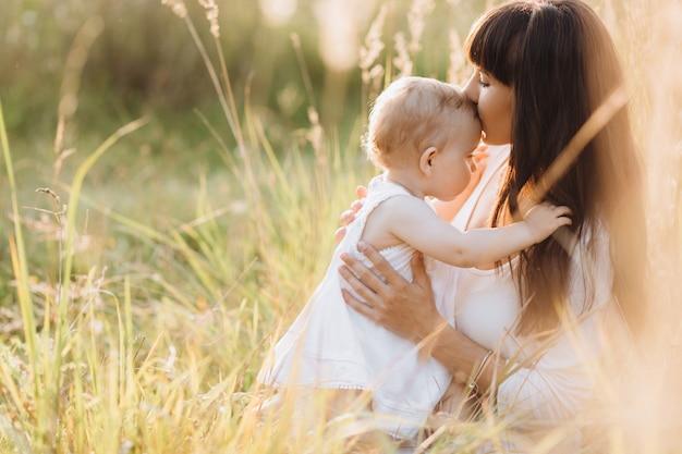 Mooi portret van charmante moeder en mooie kleine dochter lopen over het veld Gratis Foto