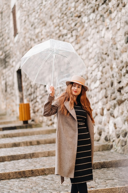 Mooi romantisch meisje in een jas en hoed met een transparante paraplu in annecy Premium Foto