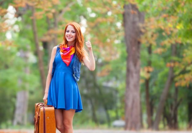 Mooi roodharigemeisje met koffer in het park. Premium Foto