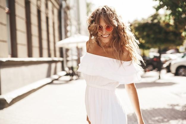 Mooi schattig blond tienermodel zonder make-up in de zomer hipster witte jurk die op straat in zonnebril loopt. draai je om en ren Gratis Foto