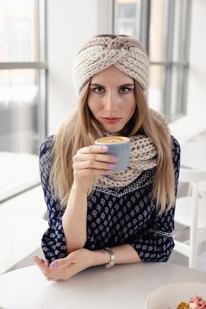 Mooi schattig winter meisje gebreide muts en wanten met koffiemok dragen. aantrekkelijk meisje met warme drank op café achtergrond. koffie drinken en genieten van het leven. Premium Foto