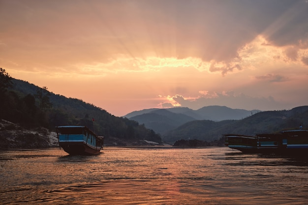 Mooi schot van de mekong rivier met boten op de voorgrond bij zonsondergang in pak beng, laos Gratis Foto