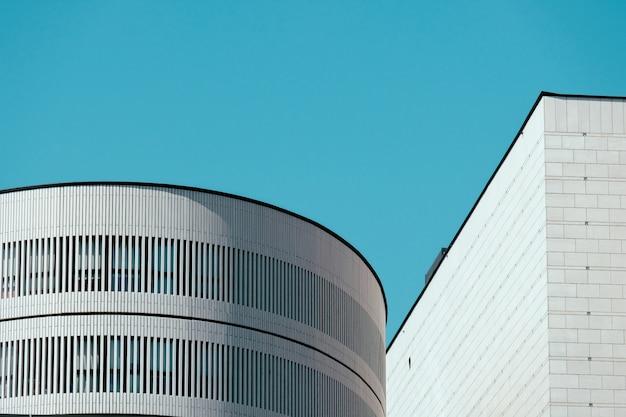 Mooi schot van de top van de witte gebouwen met heldere blauwe hemel Gratis Foto