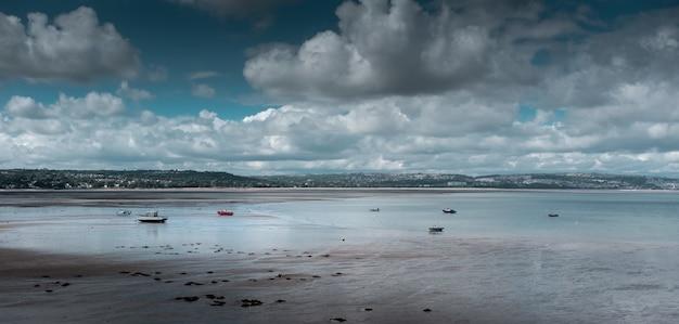 Mooi schot van een kust onder de bewolkte hemel Gratis Foto