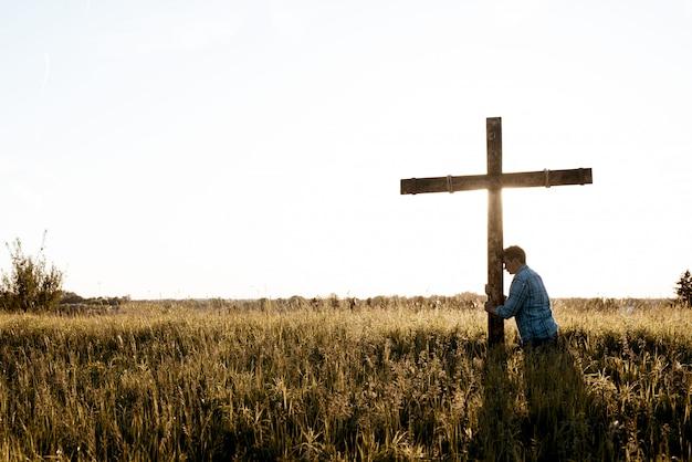 Mooi schot van een man met zijn hoofd tegen het houten kruis in een grasveld Gratis Foto