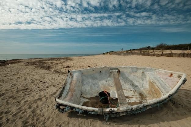 Mooi schot van een oude vissersboot op het strand op een zonnige dag Gratis Foto