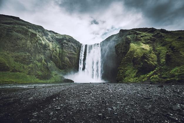 Mooi schot van een waterval die uit bergen naar beneden komt Gratis Foto