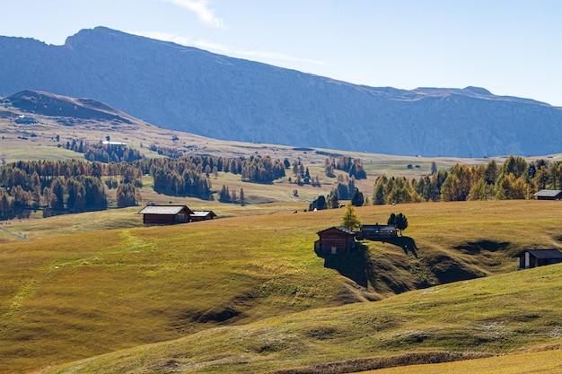 Mooi schot van gebouwen op een met gras begroeide heuvel in dolomiet italië Gratis Foto