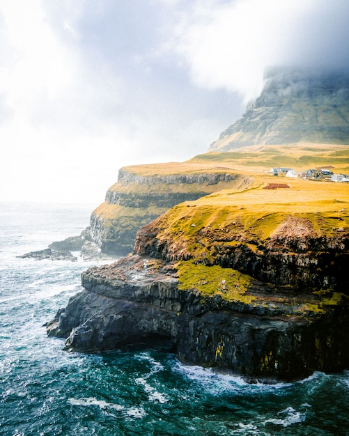 Mooi schot van groene bergen en de zee met bewolkte hemel Gratis Foto