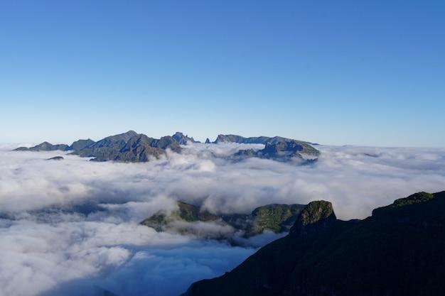 Mooi schot van groene bergen en heuvels bedekt met witte wolken in een heldere hemel Gratis Foto