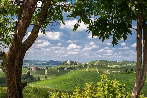 Mooi schot van groene heuvels en gebouwen in de verte onder een blauwe bewolkte hemel Gratis Foto