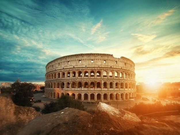 Mooi schot van het beroemde romeinse colosseum amfitheater onder de adembenemende hemel bij zonsopgang Gratis Foto