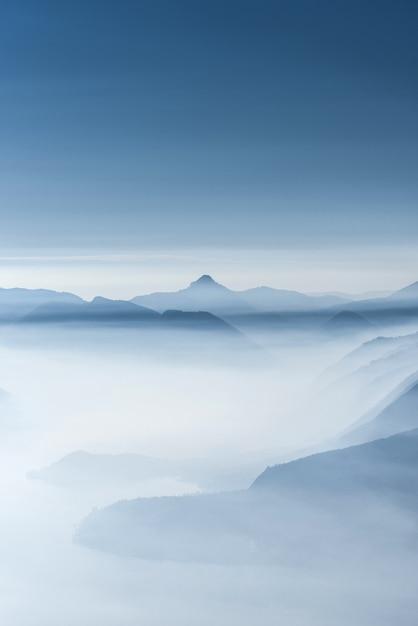 Mooi schot van hoge witte heuveltoppen en bergen bedekt met mist Gratis Foto